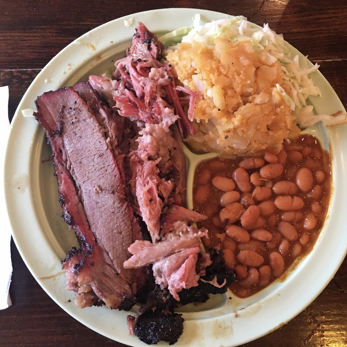 A full plate of barbeque, brisket, pulled pork, beans, potato salad